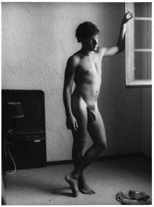 nude man looks out window