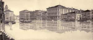 Black and white landscape of Grand Canal in Venice with mirrored reflection of Buildings on water.