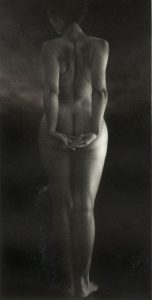 full back of female nude with hands clasped