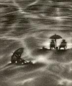 distant view of people sitting beneath umbrellas