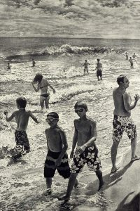boys walking on beach with others in surf at Montauk by Art Werger