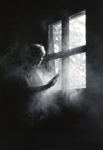 woman indoors next to window reaching for smoke