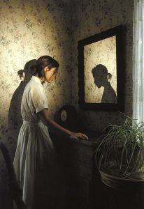woman looking into mirror where only her shadow is reflected