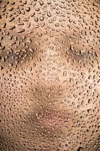 Woman's head as seen thru water droplets which in turn are body parts