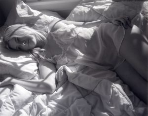 girl in nightdress laying in bed