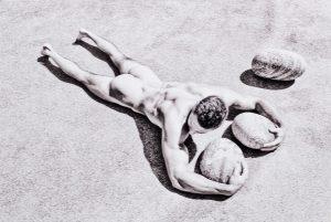 nude model from Bel Ami lies prone with rocks in Greece