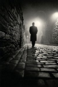 man walking alone on a cobblestone path at night
